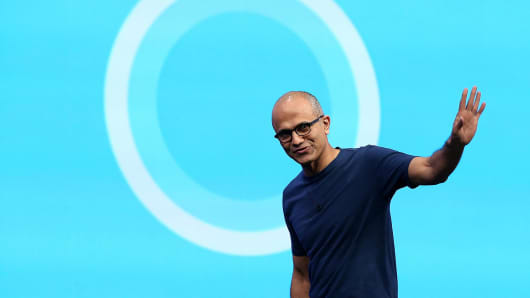 Microsoft CEO Satya Nadella walks in front of the Cortana logo.