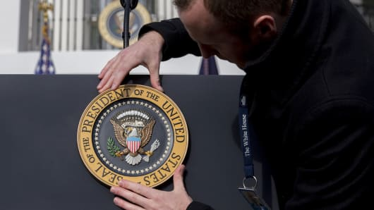 A White House staff member adjusts the presidential seal before a tax bill passage event with U.S. President Donald Trump.