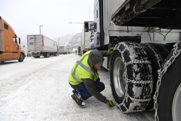 Truck driver Mike Segelke tightens up chains on his semi-truck at a chain-up station.