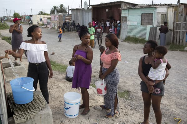 Women fetch water from a communal tap on February 8, 2018, in Khayelitsha, about 40 kilometers outside of Cape Town, South Africa.
