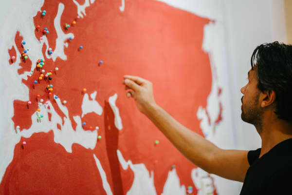 Vikram Bharati, founder of Tribe Theory, places pin on world map