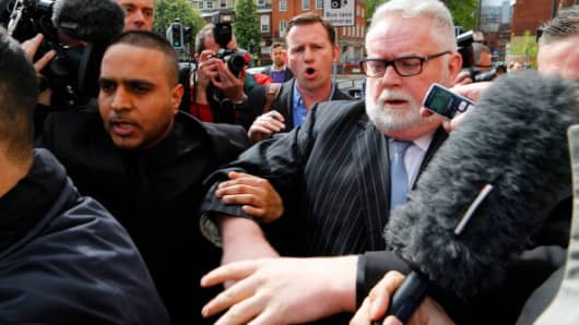 Paul Flowers, former chairman of Co-Operative Bank Plc, right, is surrounded by media as he leaves Leeds Magistrates Court in Leeds, U.K., on Wednesday, May 7, 2014.