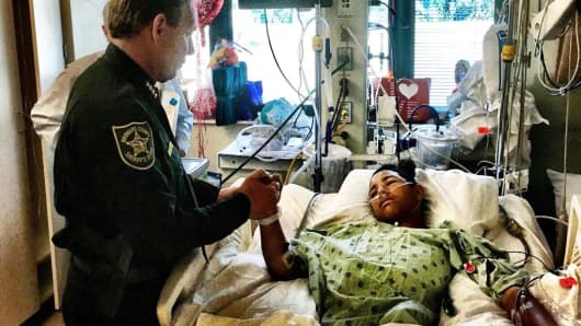 This image made available by the Broward County Sheriff's Office on Sunday, Feb. 18, 2018, shows Sheriff Scott Israel, holding the hand of Anthony Borges, 15, a student at Marjory Stoneman Douglas High School. The teenager was shot five times during the massacre on Valentine's Day that killed 17 students. Borges is being credited with saving the lives of at least 20 other students.