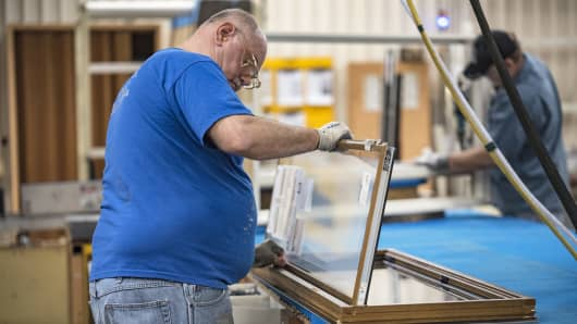 A worker installs glass to a window frame at the Pella Corp. manufacturing facility in Pella, Iowa.