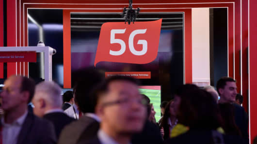 People walk by a 5G stand at the Mobile World Congress (MWC), the world's biggest mobile fair, on February 26, 2018 in Barcelona.
