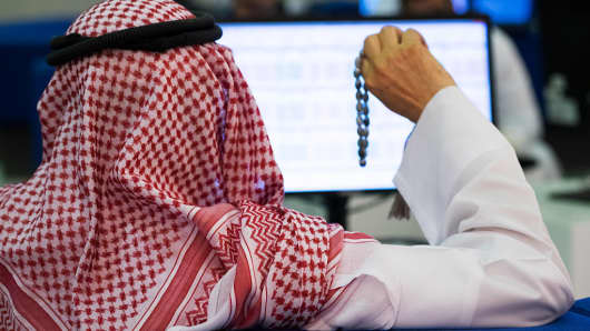 An trader plays with prayer beads as he watches a computer screen displaying financial data at the Dubai Financial Market (DFM) in Dubai, United Arab Emirates.