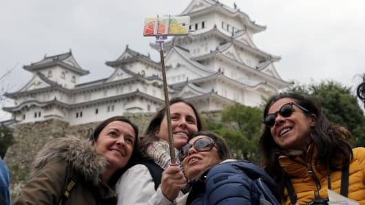 Foreign visitors take a selfie in front of the UNESCO World Heritage site Himeji Castle in Himeji, Japan