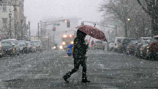 woman holds an umbrella as snow falls on March 7, 2018 in Hoboken, New Jersey. This is the second nor'easter to hit the area within a week and is expected to bring heavy snowfall and winds, raising fears of another round of electrical outages.