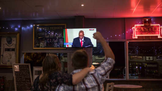 Customers in a bar watch former South African President Jacob Zuma make a live address to the nation to announce his resignation on February 14, 2018.