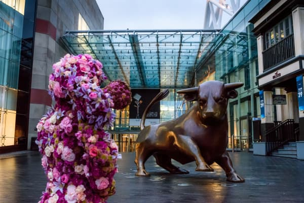 "Fearless Friend, a flower ""statue"" by GirlCrew.com, faces a statue of a bull at the Bullring shopping mall in Birmingham, U.K."