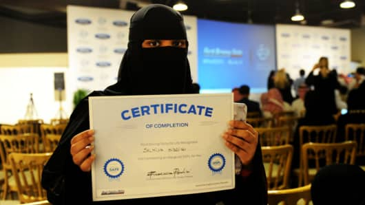 A Saudi woman poses for a photo with a certificate after completing Ford's driving course in Jeddah on March 7, 2018.