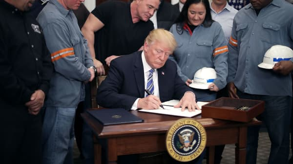 Surrounded by steel and aluminum workers, U.S. President Donald Trump (C) signs a 'Section 232 Proclamation' on steel imports during a ceremony in Roosevelt Room the the White House March 8, 2018 in Washington, DC.