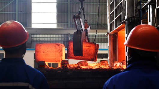 Chinese employees watch hot red steel at a steel plant in Zouping in China's eastern Shandong province on March 5, 2018.