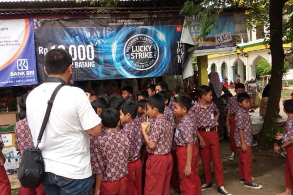 Children outside a school near Jakarta, Indonesia, are seen close to a poster advertising Lucky Strike cigarettes
