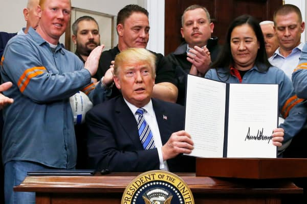 President Donald Trump holds up a proclamation during a White House ceremony to establish tariffs on imports of steel and aluminum at the White House in Washington, March 8, 2018.