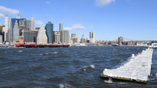 A cargo ship sails past a pier covered in snow and ice floating in the East River in Brooklyn, New York on January 5, 2018. The National Weather Service said early Friday that very cold temperatures and wind chills will follow for much of the eastern third of the US through the weekend. A cold wave gripping a large section of the United States had already been blamed for a dozen deaths.