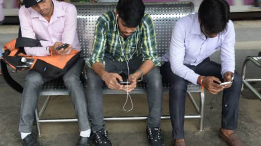 Indians surf the internet on their phones at a free Wi-Fi zone inside a suburban railway station in Mumbai on August 22, 2016.