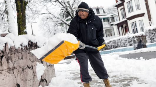 Luis Bernerdes shovels snow from a nor'easter storm off of his walkway in the Mattapan neighborhood of Boston on March 8, 2018.