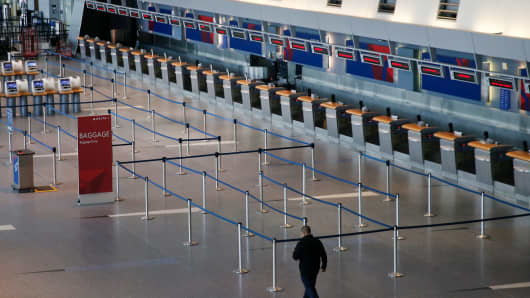 A man walks past an empty ticketing area for Delta at a deserted Logan Airport in Boston after the third nor'easter storm to hit the region in two weeks cancelled the majority of flights on March 13, 2018.