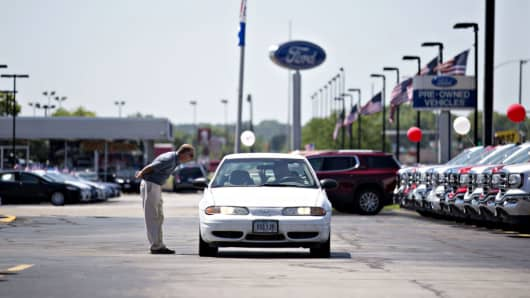 A salesman talks to a person in a vehicle at a Fiat Chrysler Automobiles (FCA) car dealership in Moline, Illinois.