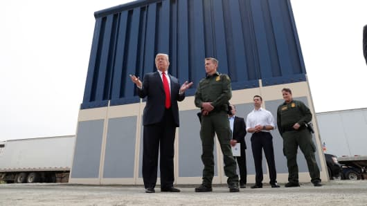President Donald Trump talks with a U.S. Customs and Border Protection (CBP) Border Patrol Agent while participating in a tour of U.S.-Mexico border wall prototypes near the Otay Mesa Port of Entry in San Diego, California, March 13, 2018.