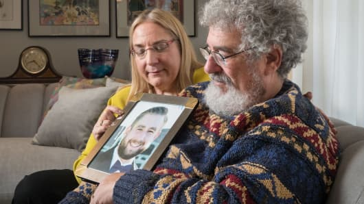 Mary Rich and her husband, Joel Rich hold a photo of their son in their home in Omaha, Nebraska, on January 11, 2017.