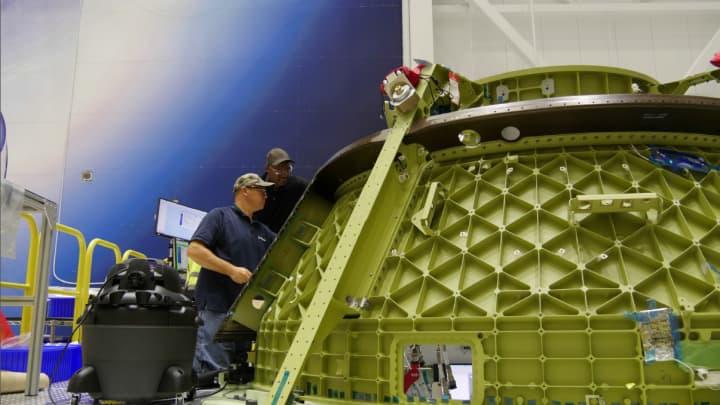 Boeing engineers work on the Starliner capsule's frame.