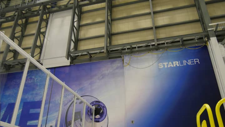 The Starliner facility's Space Shuttle-era hangar doors, where the underlying infrastructure is visible under the new Boeing remodeling.