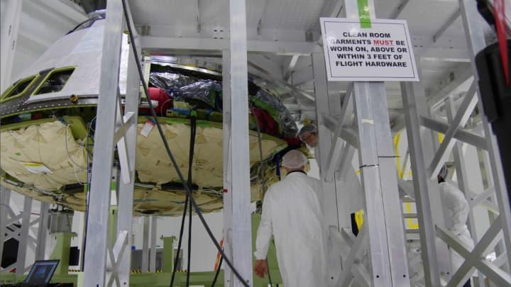 "Boeing engineers in ""bunny suits"" work on a Starliner capsule in a clean room."