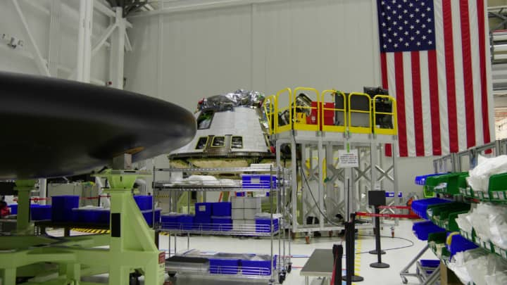 A Starliner capsule near completion, with its heat shield underbelly visible in the foreground.