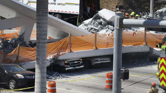 Vehicles are seen trapped under the collapsed pedestrian bridge that was newly built over southwest 8th street allowing people to bypass the busy street to reach Florida International University on March 15, 2018 in Miami, Florida.