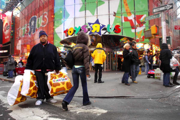 A shopper exits the Times Square Toys 'R' Us store with his purchases in New York.