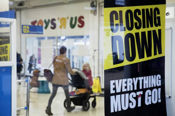 Customers pass an advertisement for a 'Closing Down' sale at a Toys 'R' Us Inc. retail store.