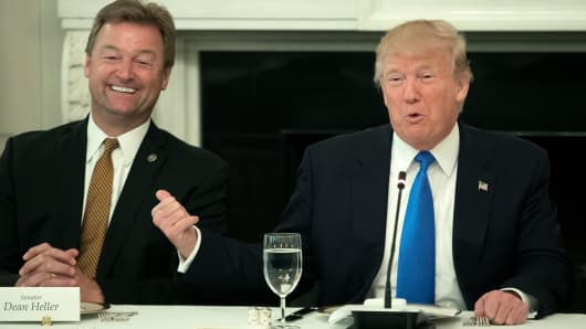 President Donald Trump (R) gestures towards Sen. Dean Heller (R-NV) (L) while delivering remarks on health care.