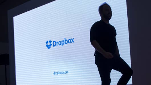 The silhouette of Drew Houston, CEO and co-founder of Dropbox Inc., is seen walking on stage during an event in San Francisco.