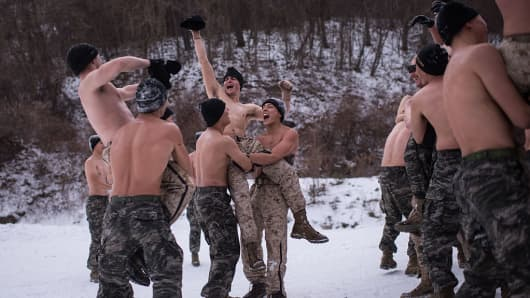 South Korean and US soldiers wrestle for photographers during a joint annual winter exercise in Pyeongchang, on January 28, 2016.