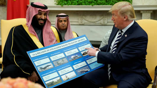 President Donald Trump holds a chart of military hardware sales as he welcomes Saudi Arabia's Crown Prince Mohammed bin Salman in the Oval Office at the White House in Washington, U.S., March 20, 2018.