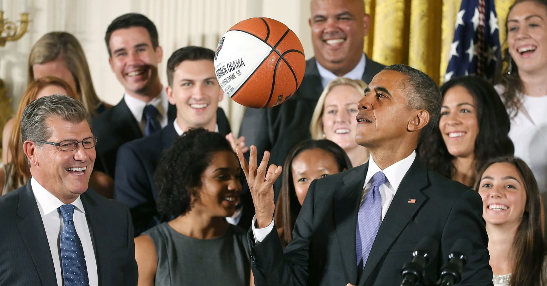 U.S. President Barack Obama tosses up a basketball given to him by coach Geno Auriemma (L) while honoring the 2015 NCAA Women's Basketball Champion University of Connecticut Huskies.