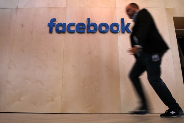 A man walks in front of the Facebook logo at the Facebook Innovation Hub.