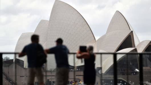 Tourists take pictures of the Sydney Opera House in Sydney, Australia on Feb. 13, 2018. Credit Suisse highlighted the tourism sector as an opportunity in the Australian market.