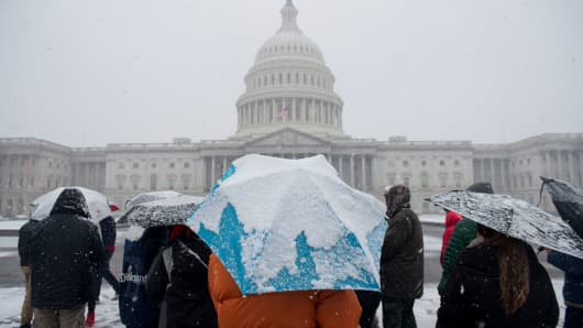Tourists visit the US Capitol during a snow storm in Washington, DC, March 21, 2018. The fourth Noreaster in less than three weeks, Winter Storm Toby, is throwing a fresh blanket of snow just as spring begins.