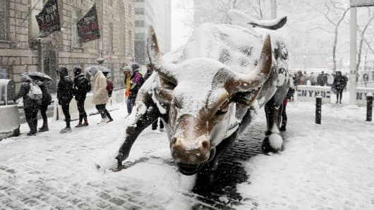 Pedestrians walk past a snow covered bull sculpture during a late season nor'easter in New York.