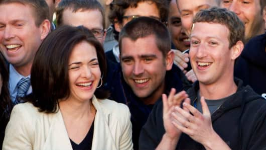 Mark Zuckerberg, chief executive officer of Facebook Inc., right, Sheryl Sandberg, chief operating officer of Facebook, left, applaud after remotely ring the opening bell for trading at the Nasdaq MarketSite from the Facebook campus in Menlo Park, California