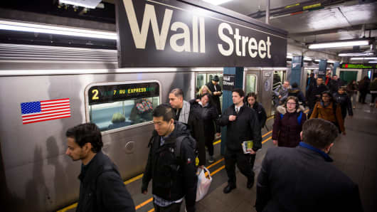 Commuters exit a train at a Wall Street subway station near the New York Stock Exchange.