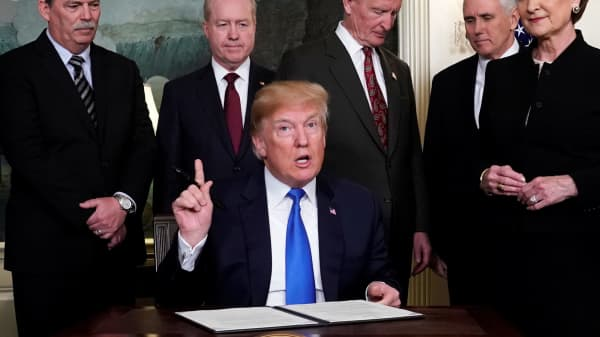 President Donald Trump, surrounded by business leaders and administration officials, prepares to sign a memorandum on intellectual property tariffs on high-tech goods from China, at the White House in Washington, U.S. March 22, 2018.