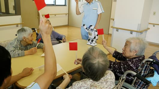 Residents of a nursing home play with a Humanoid robot 'PALRO', manufactured by Fujisoft Incorpopated, at the nursing home in Yokohama city, Kanagawa prefecture, Japan.