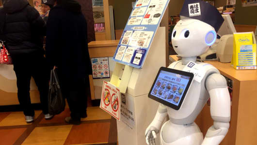 Pepper, a humanoid robot developed by SoftBank Group Corp., moves around on its own to guide passengers at sushi shop in Tokyo, Japan.