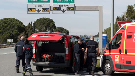 French police and firefighters secure the entrance of Trebes, southern France, where an armed man took hostages in a supermarket, Friday, March 23, 2018.