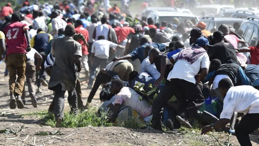 Supporters the Kenyan opposition run away from teargas on November 28, 2017, during demonstrations in a suburb of the capital Nairobi.