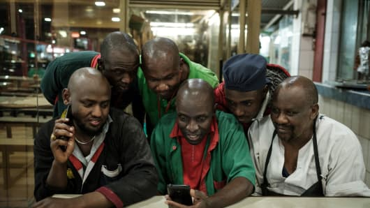 People watch the campaign video of Kenya's opposition presidential candidate Raila Odinga on a smartphone in Nairobi on September 5, 2017.